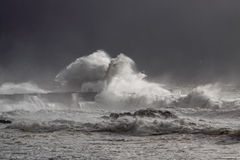 Stormy waves over old lighthouse and pier Stock Photo