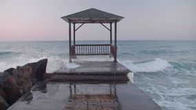 Stormy waves and pier. Shot of a concrete dock extending out into the water on a lake or sea. Stormy sea shot in 4k stock footage