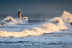 Stormy Waves at Tynemouth Lighthouse. A stormy sea hits Tynemouth North Pier, resulting in high crashing waves cascading into the mouth of the River Tyne Royalty Free Stock Photography