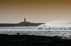 Stormy Weather. Lighthouse during stormy weather with waves in front stock photos