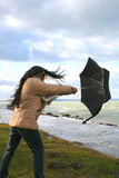 Stormy weather. Digital photo of a woman with an umbrella at a stormy sea Stock Photography