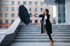 Stormy weather. Black girl catch flying umbrella Stock Images