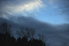 Stormy weather clearing with crescent moon Stock Photo