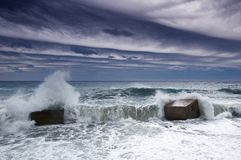Stormy weather and a concrete structure coastline barrier with the sea beyond Stock Photography