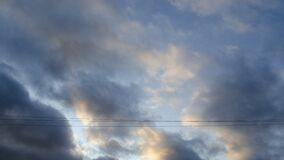 Stormy weather. Dark cloud on the sky. Sunlight reflected on the clouds. Two wire lines. Background for text or design