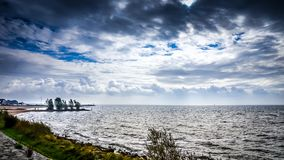 Stormy weather and dark clouds over het IJsselmeer in the Netherlands. Stormy weather and dark clouds hanging over het IJsselmeer at the historic fishing village stock photography