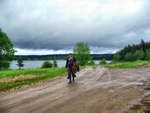 Stormy weather - Fisherman with gear. Walking back to the camp, no fish caught today Stock Image
