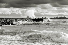 Stormy weather near sea. A black and white picture of a stormy sea of which strong foamy waves hit a mule. Tallinn city panorama at background Stock Image