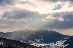Stormy weather over rural area in mountains. Stormy winter sky over rural area in mountains near spruce forest royalty free stock image