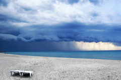 Stormy weather with rain on the beach. With two chairs. Before a powerful storm royalty free stock image