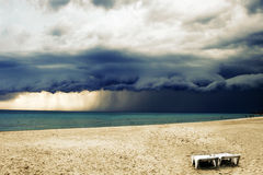 Stormy weather with rain on the beach. With two chairs. Before a powerful storm royalty free stock photography