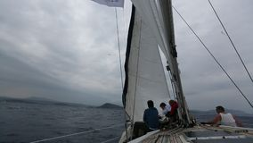 In stormy weather sailors participate in sailing regatta stock video footage