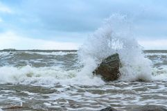 Stormy weather by the sea, sea wave beats on a stone. Sea wave beats on a stone, stormy weather by the sea stock photos