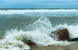 Stormy weather by the sea, sea wave beats on a stone. Sea wave beats on a stone, stormy weather by the sea stock photo