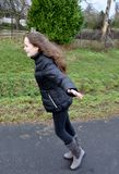 Girl tries to fly in the storm. Stormy weather, teenage girl outside she has fun and tries to fly with wide spread arms Stock Photography