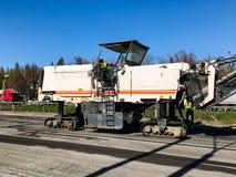 Storskaligt reparationsarbete med stort maskineri på huvudvägen Arkivfoton