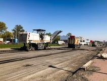 Storskaligt reparationsarbete med stort maskineri på huvudvägen Royaltyfria Foton