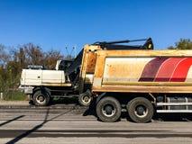 Storskaligt reparationsarbete med stort maskineri på huvudvägen Arkivbild