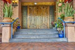 Storslagen entryway som markeras av stora dubbla wood dörrar Arkivfoto