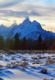 Storslagen sikt för Tetons kluven stångstaket på alpenglowskymningsolnedgången under linsformade moln i den storslagna Tetons nat royaltyfri bild
