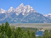 Storslagen Tetons nationalpark i Wyoming, Förenta staterna; mäktig sikt för bergmaximum med snö, solen och floden arkivfoton