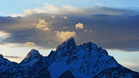 Storslagna Tetons på alpenglowskymningsolnedgången under linsformade moln i den storslagna Tetons nationalparken i Wyoming royaltyfri bild