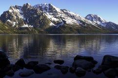 Storslagna Tetons reflekterad i Jenny Lake med vaggar Royaltyfri Foto