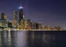 Storstadhorisont på natten med ljus tände upp längs vattenshoreline Arkivbilder