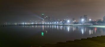Storstadhorisont på natten med ljus tände upp längs vattenshoreline Arkivfoton