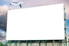 Stort affischtavlavitmellanrum och flygplan på himmel arkivbilder