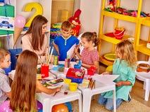 Stort av barn med lärarekvinnamålning på papper i dagis Royaltyfria Bilder