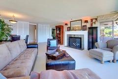 Stort bekvämt vardagsrum med den stora bruna sofaen. Arkivfoto