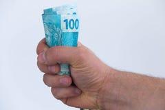 Stort belopp av brasilianska pengar i handen, begrepp av framgång Fotografering för Bildbyråer