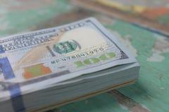 Stort belopp kassa av hundra US dollarsedlar som sätter på träpanelbakgrund arkivbild