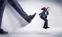 Stort ben som sparkar den lilla mannen arkivfoton