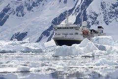 Stort blått turist- skepp i isen i bakgrunden av Antarcen Arkivfoton
