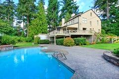 Stort brunt hus som är yttre med den sommarträdgården och simbassängen Royaltyfria Foton