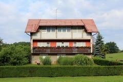 Stort delvist oavslutat förorts- familjhus med den långa balkongen som omges med gräs och träd royaltyfri fotografi