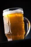 Stort exponeringsglas av öl över en mörk bakgrund Royaltyfri Bild