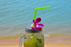 Stort exponeringsglas av mojito med orkidéblomman på stranden Royaltyfri Foto
