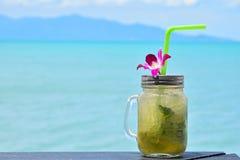Stort exponeringsglas av mojito med orkidéblomman på stranden Arkivbilder