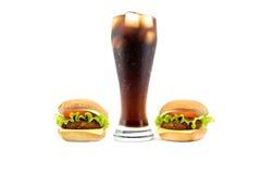 Stort exponeringsglas av sodavatten bredvid två hamburgare på sidorna som isoleras på vit Arkivfoton