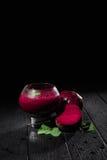 Stort exponeringsglas med bordeaux-färgade coctailar på en svart bakgrund Sund milkshake med rödbeta, mintkaramellen och socker k royaltyfri bild
