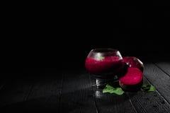 Stort exponeringsglas med bordeaux-färgade coctailar på en svart bakgrund Sund milkshake med rödbeta, mintkaramellen och socker k royaltyfria foton