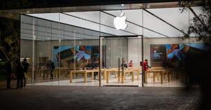 Stort exponeringsglas Windows av Apple Store på modernt byggnadsfolk för natt som arbetar på den datorApple logoen arkivfoto