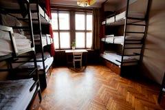 Stort fönster i dormrummet av det europeiska vandrarhemmet för student med jämna sängar royaltyfri bild