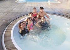 Stort familjfolk och bröder som kopplar av i vattenpöl med happ Royaltyfria Bilder