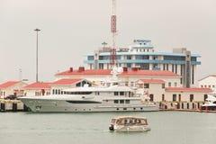 Stort fartyg och litet fartyg på bakgrunden av byggnaden av Rosmorport Sochi Arkivfoton