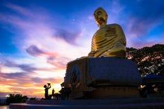 Stort guld- Buddhastatysammanträde på den Lotus betydelsen på solnedgången Arkivfoto