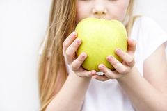 Stort gult grönt äpple i händer för barn s på vit bakgrund royaltyfri foto